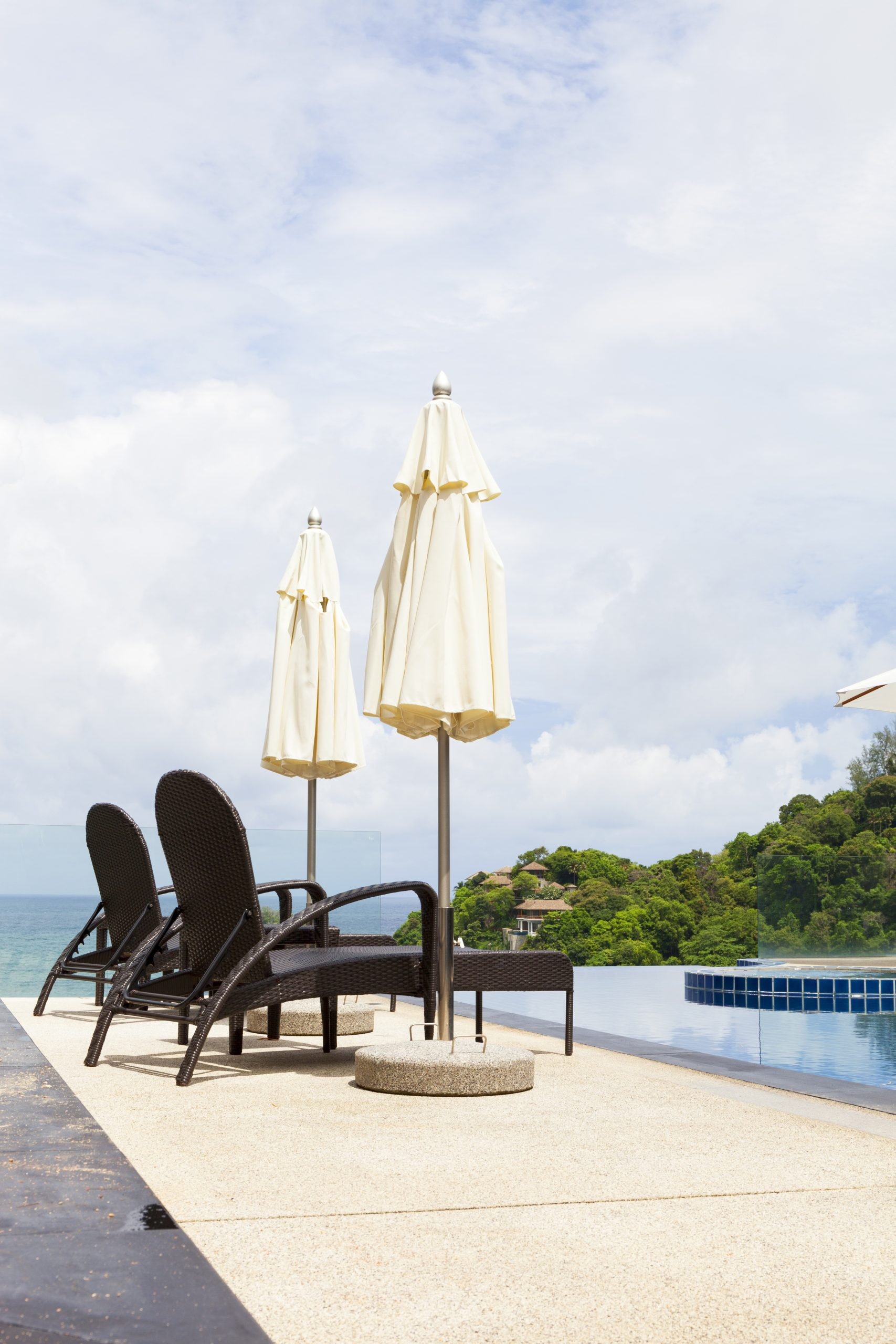 loungers next to a swimming pool with glass pool safety fencing