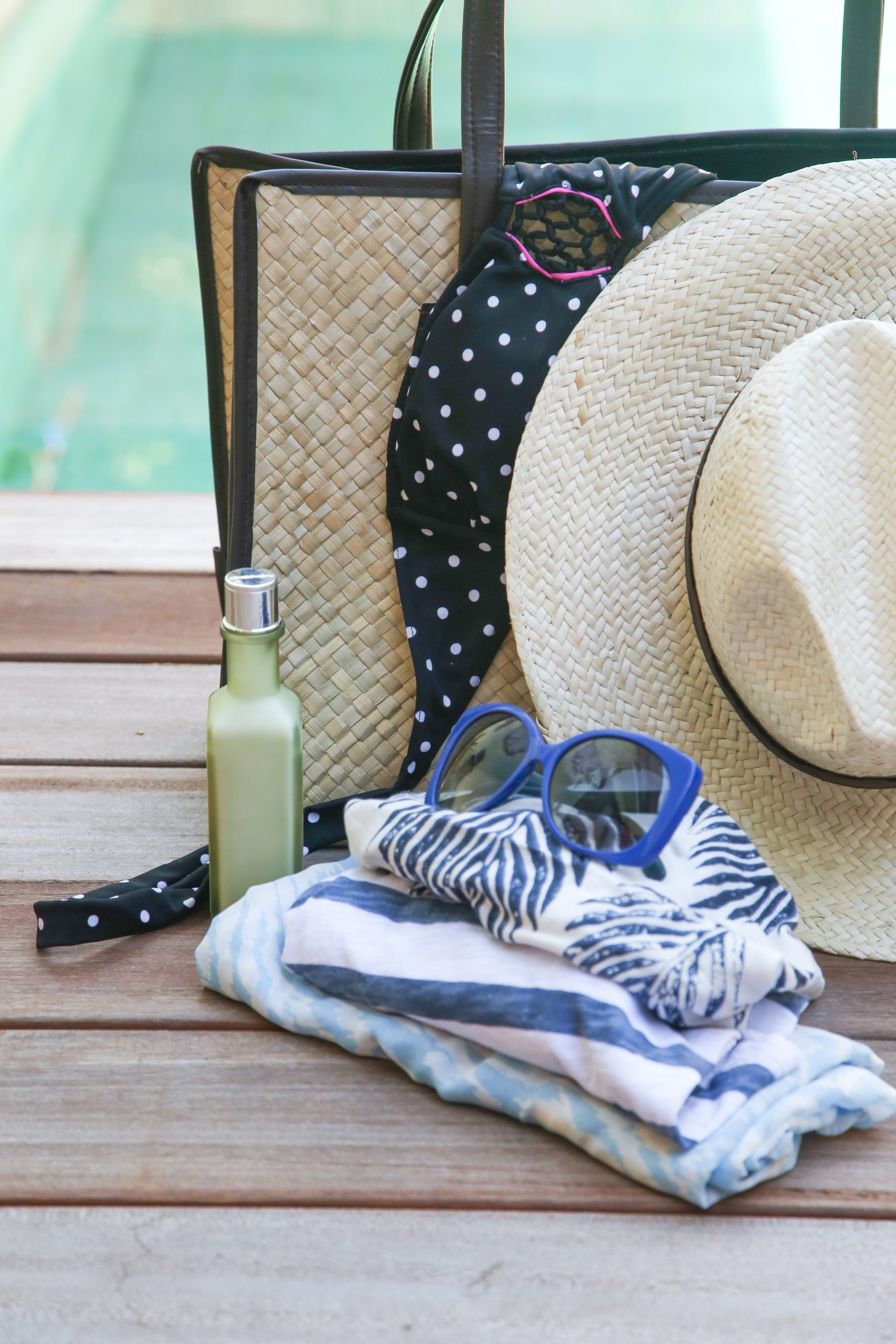 pool bag with sunglasses and hat next to swimming pool